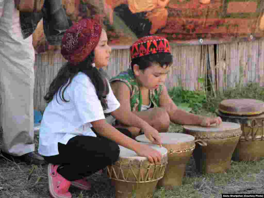 Children wearing traditional Central Asian hats play the drums