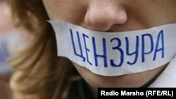 "A woman attends a protest in Russia against Internet censorship, with a sign over her mouth reading ""censorship."""