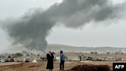 Smoke rises from the the Syrian town of Kobani after a strike from a US-led coalition against Islamic State militants who are besieging the city.