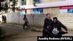 A man is stopped while trying to raise the black flag of the Islamic State group at an opposition rally in Baku in October. Baku has attempted to crack down on citizens joining militant groups.