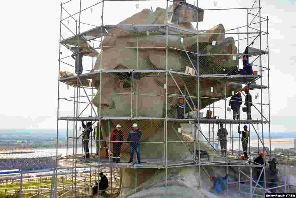 Teams of restorers at work on the monument's head in September.