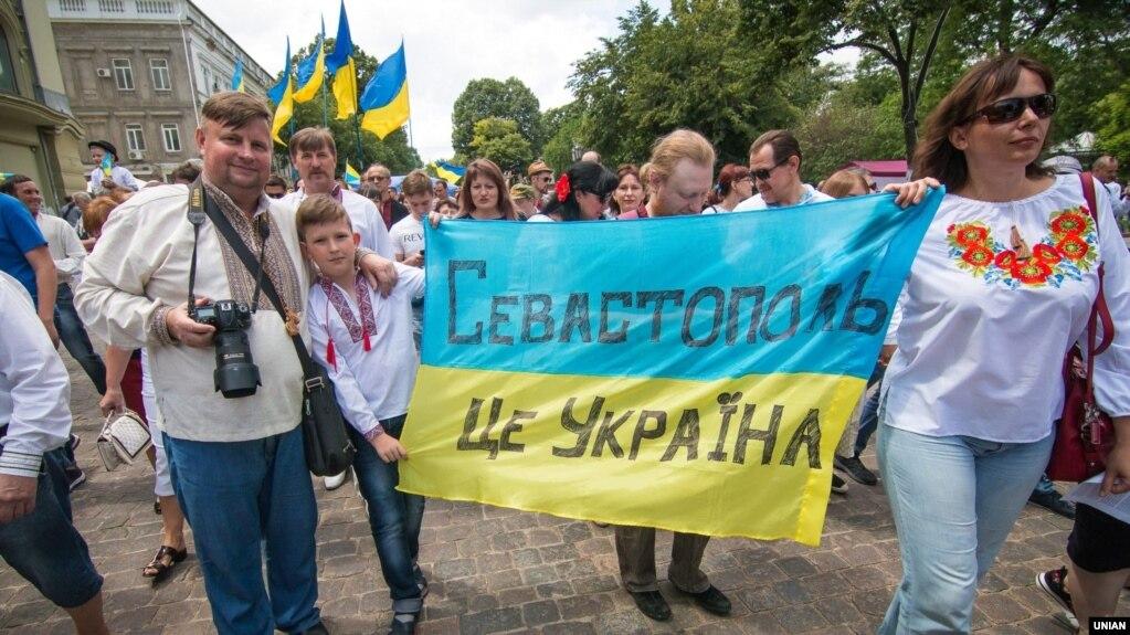 """Участники марша за территориальную целостность Украины несут ткань в цветах украинского флага с надписью: """"Севастополь- это Украина"""". Одесса, 19 мая 2018 года."""