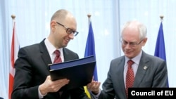 Ukrainian Prime Minister Arseniy Yatsenyuk (left) and European Council President Herman Van Rompuy exchange documents at the signing ceremony in Brussels on March 21.