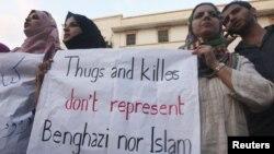 Ливиялык демонстранттар Бенгазидеги АКШ консулдугуна кол салуу кезинде Кошмо Штаттардын элчсинин өлтүрүлүшүн айыптаган плакаттарды кармап турушат. 12-сентябрь 2012