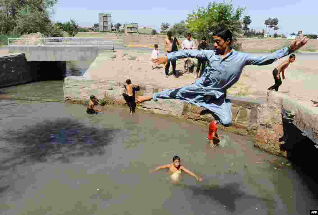 Young men cool off in a river in the Afghan city of Herat on July 29.