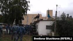 Билік өкілдері үйді сүруге қарсылық білдіріп, шатырға шығып алған әйелдерді күшпен түсіріп жатыр. Астана, 15 тамыз 2014 жыл.