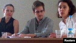 Гражданин США Эвард Сноуден (в центре), Сара Харрисон (слева) из WikiLeaks общаются с правозащитниками в аэропорту Шереметьево в Москве. 12 июля 2013 года.