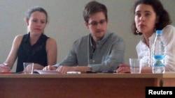 Эдвард Сноуден (ортада) Шереметьево әуежайында ресейлік және шетелдік құқық қорғаушылармен кездесіп отыр. Мәскеу, 12 шілде 2013 жыл.