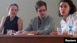 """Эдвард Сноуден (ортада) """"Шереметьево"""" әуежайында құқық қорғаушылармен кездесіп отыр. 12 шілде 2013 жыл."""