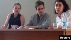 Former U.S. intelligence agency contractor Edward Snowden (center) and Sarah Harrison (left) of WikiLeaks speak to human rights representatives in Moscow's Sheremetyevo Airport on July 12.