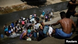 Жители обесточенного Каракаса, где нет и водоснабжения, собирают жидкость из городской сточной канавы