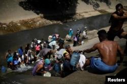 Жители Каракаса, где часто нет электричества и водоснабжения, собирают жидкость из городской сточной канавы