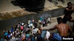 Электр кубаты жок Каракастын жашоочулары саркынды суу аккан каналдан суу алып жатышат. 11-март, 2019-жыл.