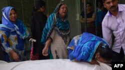 Relatives of Aftab Bahadur Masih mourn beside his body after his execution in Lahore.