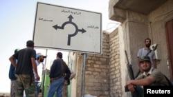 """Ливийские повстанцы у указателя с надписью """"Триполи"""""""