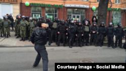 Një protestues duke gjuajtur me gurë në drejtim të një banke ruse në Kiev të Ukrainës, derisa policia qëndron para objektit