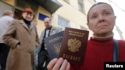 A woman poses with a Ukrainian and a Russian passport outside an office of the Russian Federal Migration Service, where she received a Russian passport, in the Crimean city of Simferopol in April.