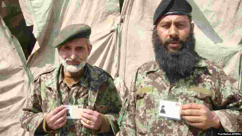 Two Afghan soldiers show off their new voter cards.