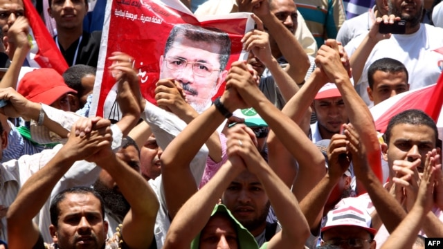 Supporters of the Muslim Brotherhood's presidential candidate Muhammad Morsi hold his portrait during a demonstration on Cairo's Tahrir Square