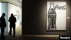 Люди стоят возле вывески логотипа компании Coca Cola. Иллюстративное фото.
