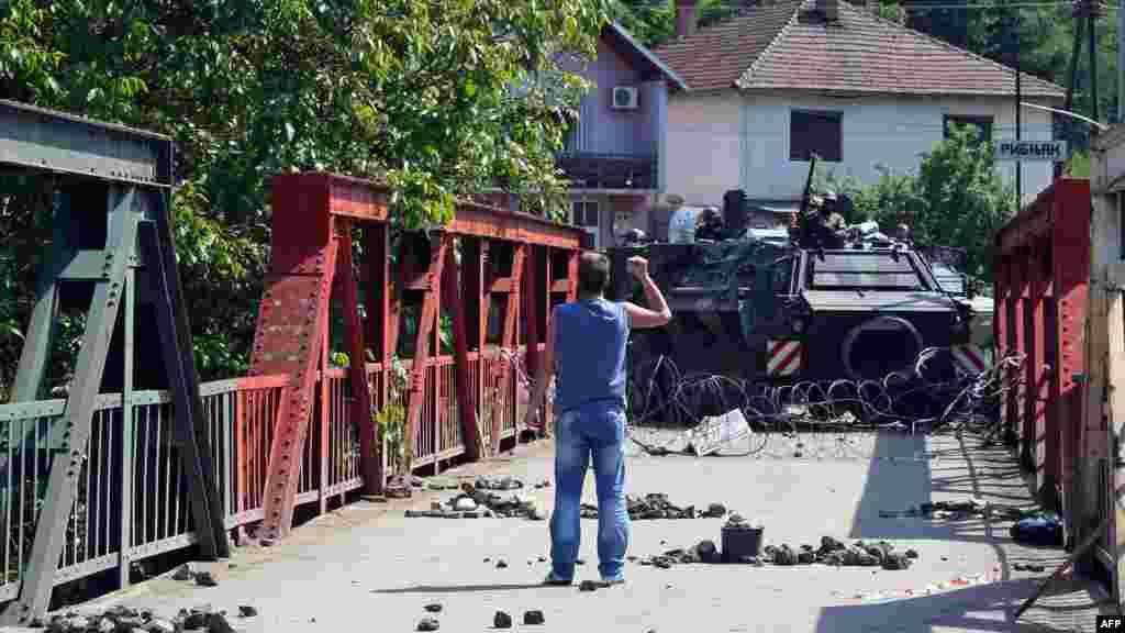 Косовский серб перед БТРом германских сил в составе KFOR, которые охраняют мост в деревне Рударе на севере Косова, 1 июня. Один военнослужащий НАТО и трое косовских сербов получили ранения в ходе столкновений, возникших из-за того, что силы НАТО попытались разобрать баррикады, которые соорудили сербы на севере Косова в попытке блокировать КПП с Сербией для албанских властей в Приштине. (AFP)