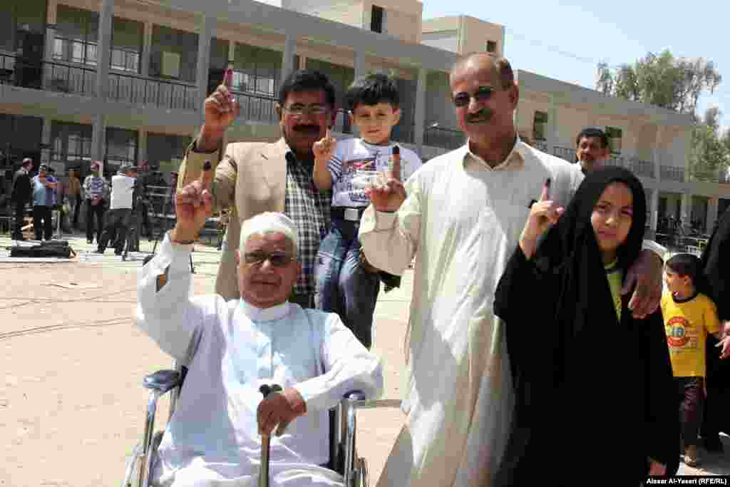 People show their ink-stained fingers after casting their votes during provincial council elections in Najaf.