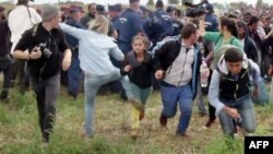A video grab shows Petra Laszlo appearing to kick a child as she ran with other migrants from a police line during disturbances at Roszke in southern Hungary.