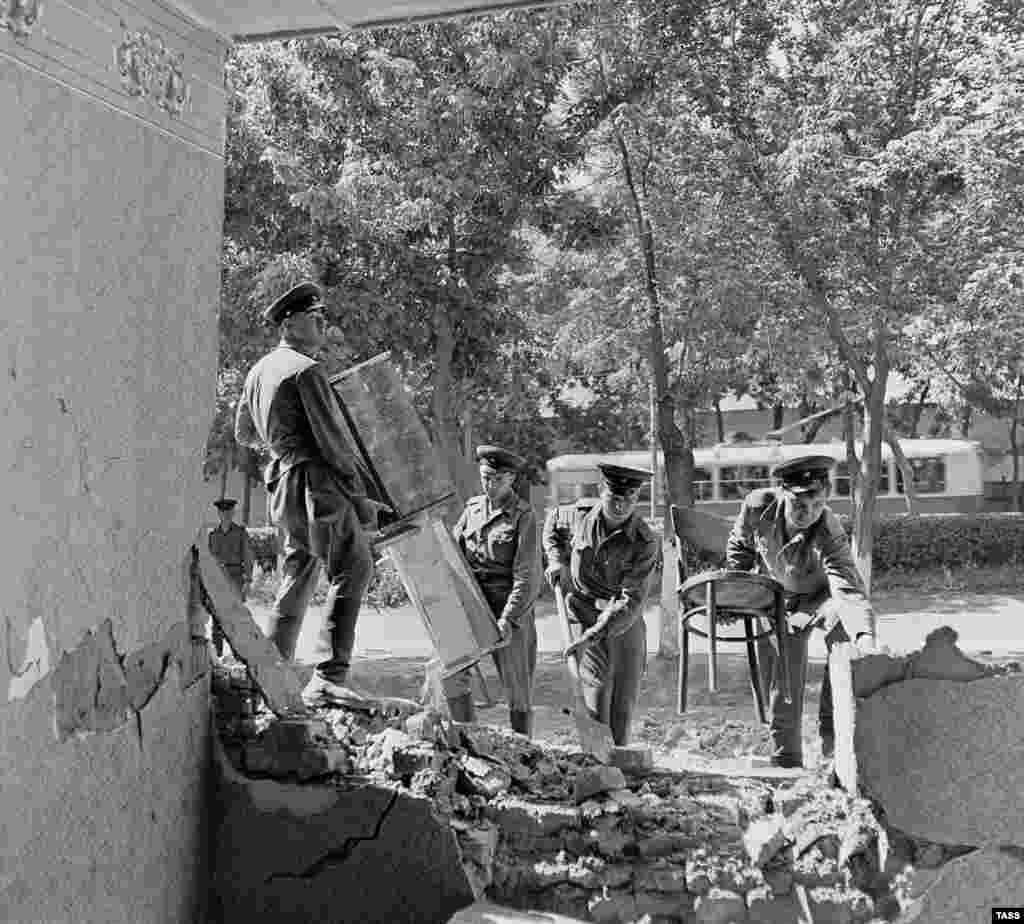 Военнослужащие разбирают разрушенный дом в центре города.