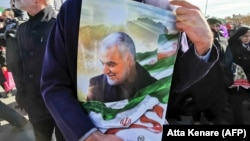 IRAN -- An Iranian man carries a portrait of slain Iranian General Qasem Soleimani, on the 40th day of his killing in a U.S. drone strike, during commemorations marking 41 years since the Islamic Revolution, in Tehran, February 11, 2020