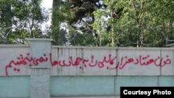 """Graffiti reads: """"We will never forgive the warlords for the blood they shed of 70,000 people in Kabul,"""" sprayed on a wall at Kabul University"""