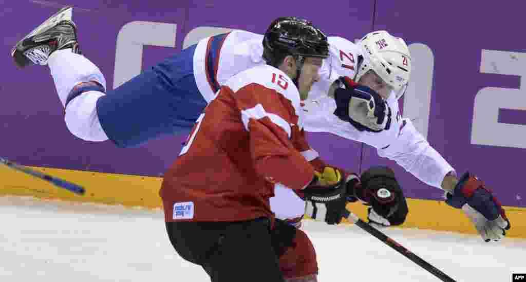 Австрійський хокеїст Мануель Латуса (попереду) змагається за шайбу з Мортеном Аском із Норвегії