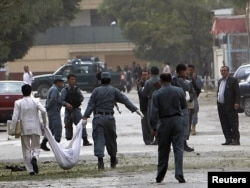 Afghan policemen carry the body of a suicide attacker at the site of a suicide attack in Kabul's embassy district which the United States says was carried out by the Haqqani network.