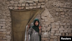 A Pashtun girl looks out from the doorway of her family dwelling in Peshawar.
