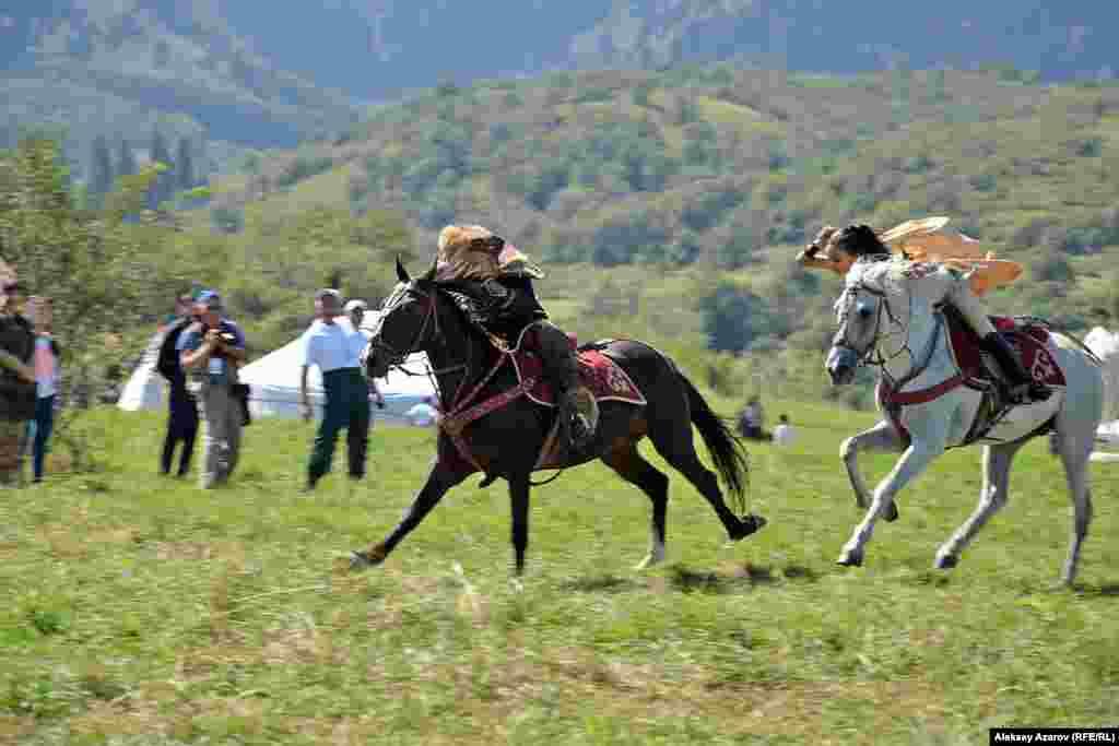 """Много чего еще увидели зрители во время показательных выступлений – джигитовку, рукопашную борьбу на лошадях, стрельбу из лука и метание копья со скачущей лошади, игру """"Догони девушку"""". Момент последнего изображен на фотографии. Девушка, догоняющая джигита, замахивается, чтобы ударить его камчой."""