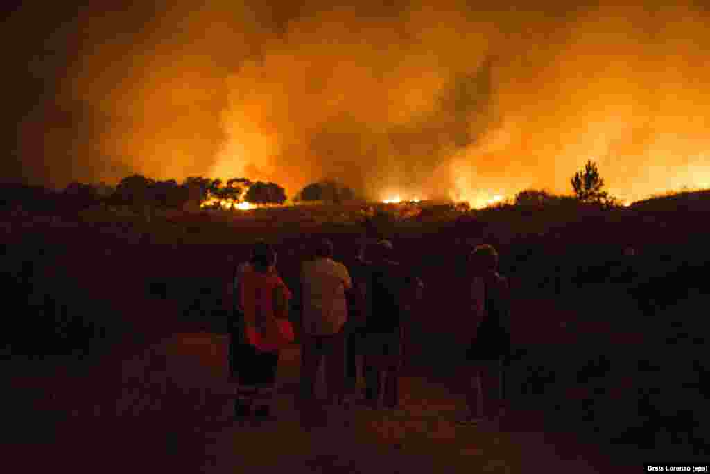 Residents of the village of Vilardevos in northwestern Spain observe a large forest fire that prompted warnings from authorities. (epa/Brais Lorenzo)