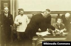 В'ячеслав Молотов у присутності Йосипа Сталіна та Йоахіма фон Ріббентрола підписує Договір про дружбу і кордон між СРСР та Німеччиною. Москва, Кремль, 23 серпня 1939 року
