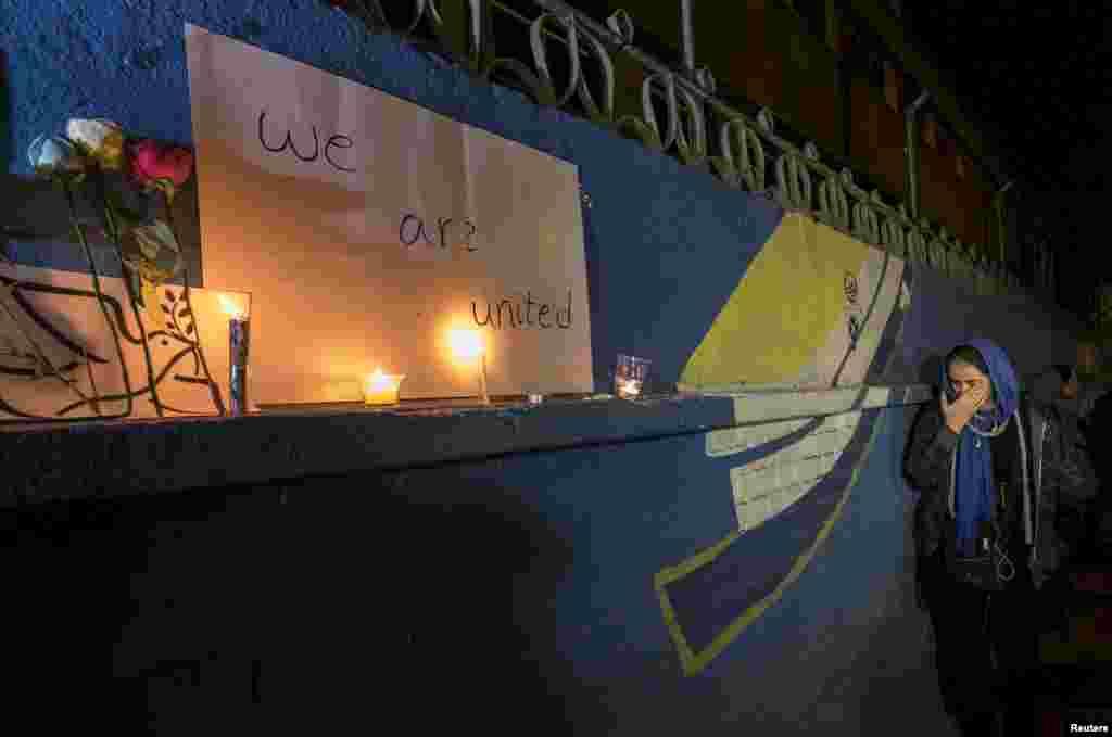 Тегерандағы француз елшілігіне Париждегі террорлық шабуылдар құрбандары құрметіне әкелінген гүлдер мен шырақтардың жанында тұрған әйел. Плакатта ағылшын тілінде «Біз біргеміз» деп жазылған. Иран, 14 қараша 2015 жыл.