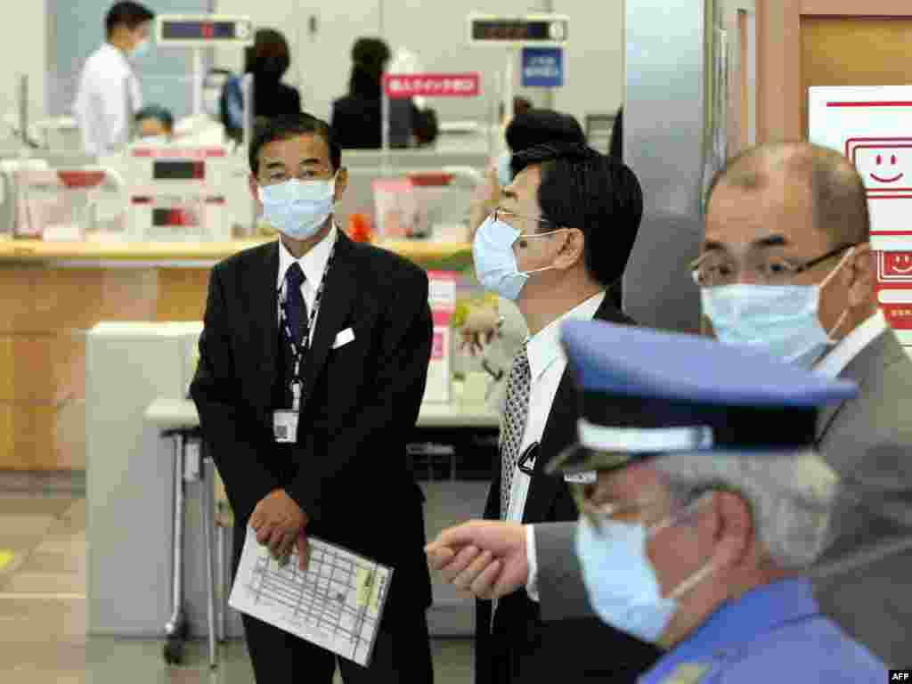 Japan - Maske potrebne? - Ovi zaposlenici banke u Kobeu su, nakon informacije da je jedan kolega inficiran virusom nove gripe, odlučili da maskama na licu povećaju mjere predostrožnosti.