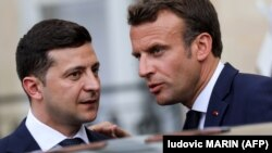 Ukrainian President Volodymyr Zelensky (left) talks with French President Emmanuel Macron as he leaves the Elysee presidential palace following their meeting in Paris on June 17.