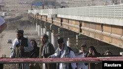 Afghans cross a border bridge over the Pyanj River into the Tajik town of Lower Pyanj, 26Aug2007