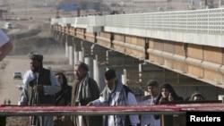 Afghans cross a border bridge over the Pyanj River into the Tajik town of Lower Pyanj, 26Aug2007