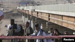 Afghans cross a bridge over the Pyanj River into Tajikistan and the the town of Lower Pyanj. (2007 photo)