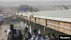 File photo of Afghans crossing a newly built border bridge over the Pyanj River into the Tajik town of Lower Pyanj.