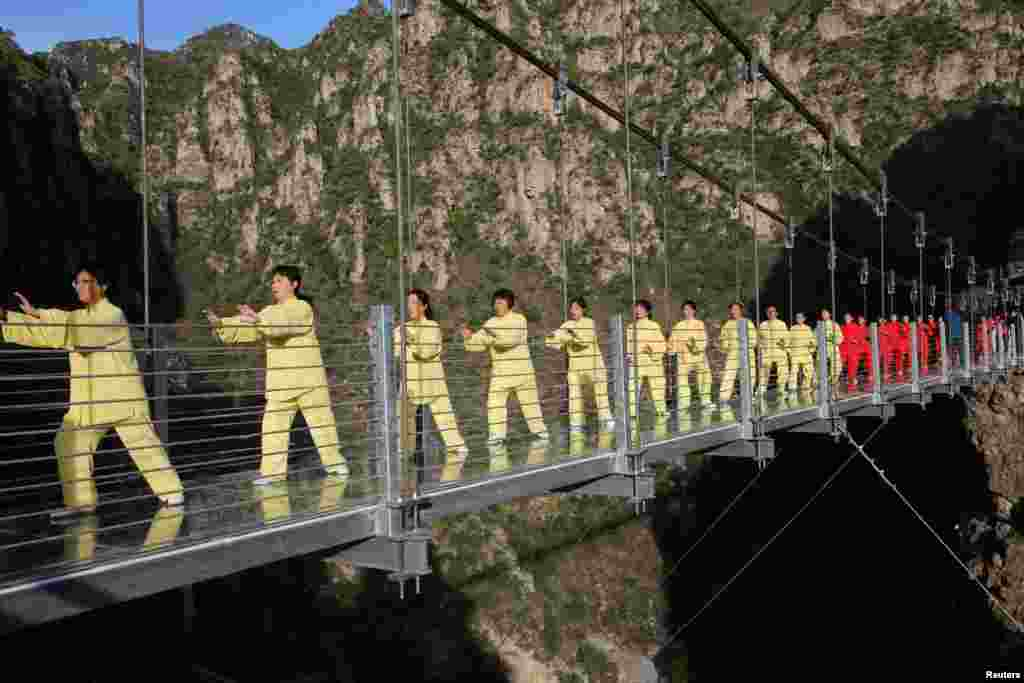 People practice tai chi on a suspension bridge during an event at a tourist spot in Beijing, China. (Reuters)