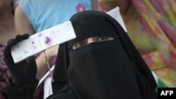 A veiled woman holds up her mobile phone. In Pakistan's conservative former tribal areas and beyond, women have become easy targets of schemes to illegally clone mobile SIM cards. (file photo)