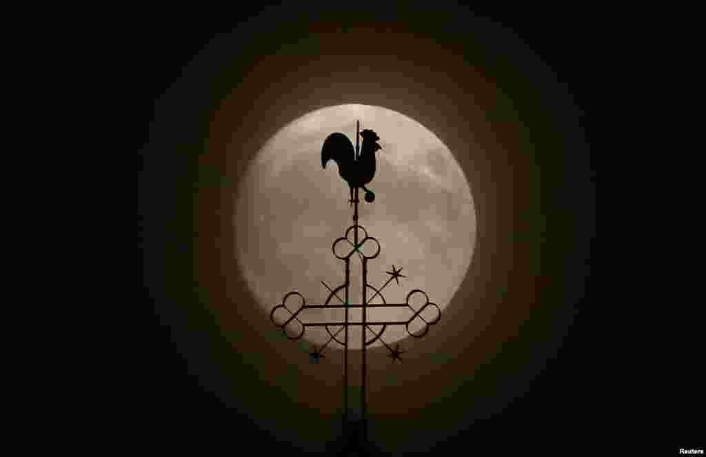 Флюгер на храме Петра и Павла на фоне луны. Городок Клайн-Аугайм, Германия.