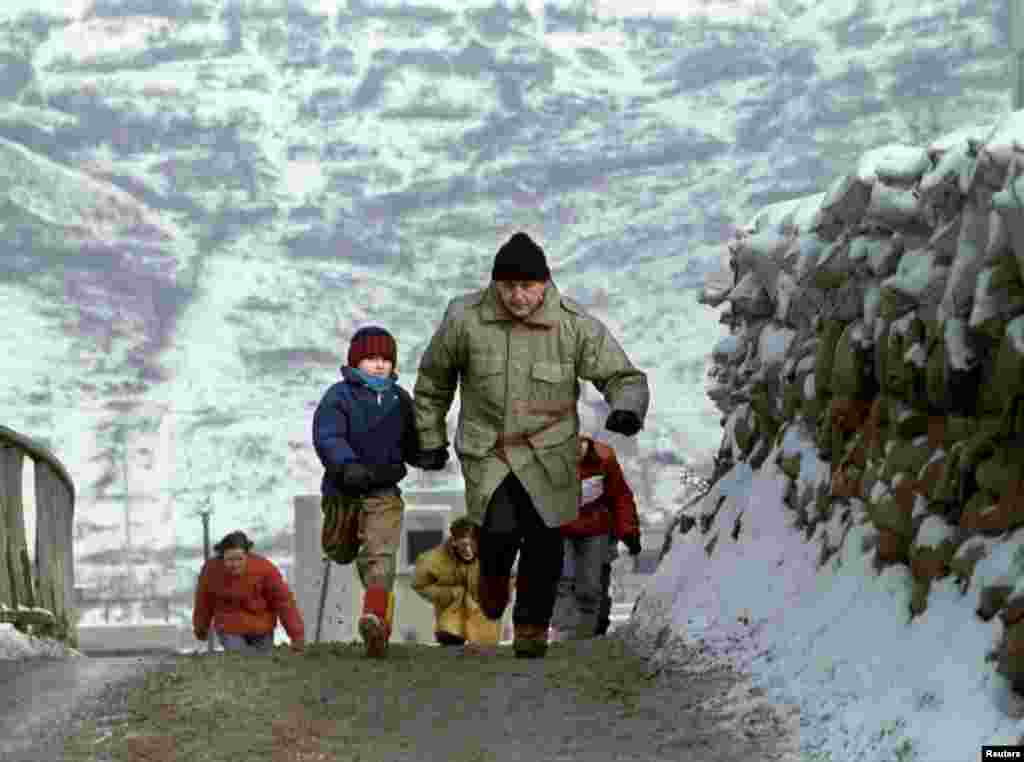 In an attempt to dodge snipers, a father and son sprint across a sandbagged bridge in the Olympic village area of Dobrinja, on January 4, 1993.