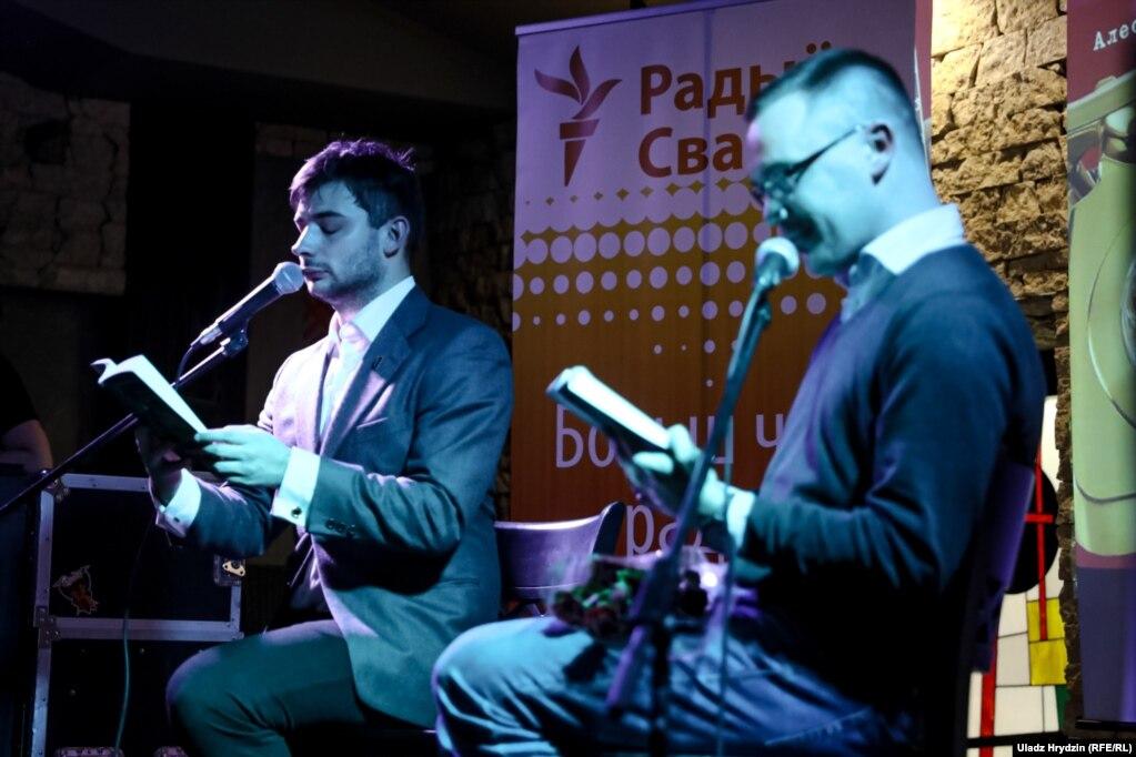 Вядучы імпрэзы актор Аляксей Сапрыкін і аўтар Алесь Пілецкі чытаюць дыялёг з кнігі.
