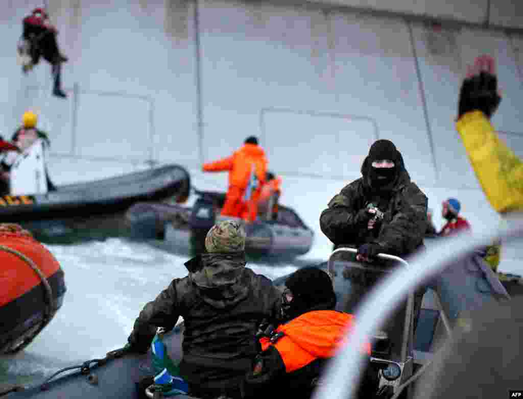 A masked Russian Coast Guard officer points a gun at a Greenpeace International activist (partially visible in lower right corner) during an attempt by environmentalists to climb aboard a Gazprom oil platform in the Pechora Sea in the Russian Arctic. (AFP/Greenpeace/Denis Sinyakov)