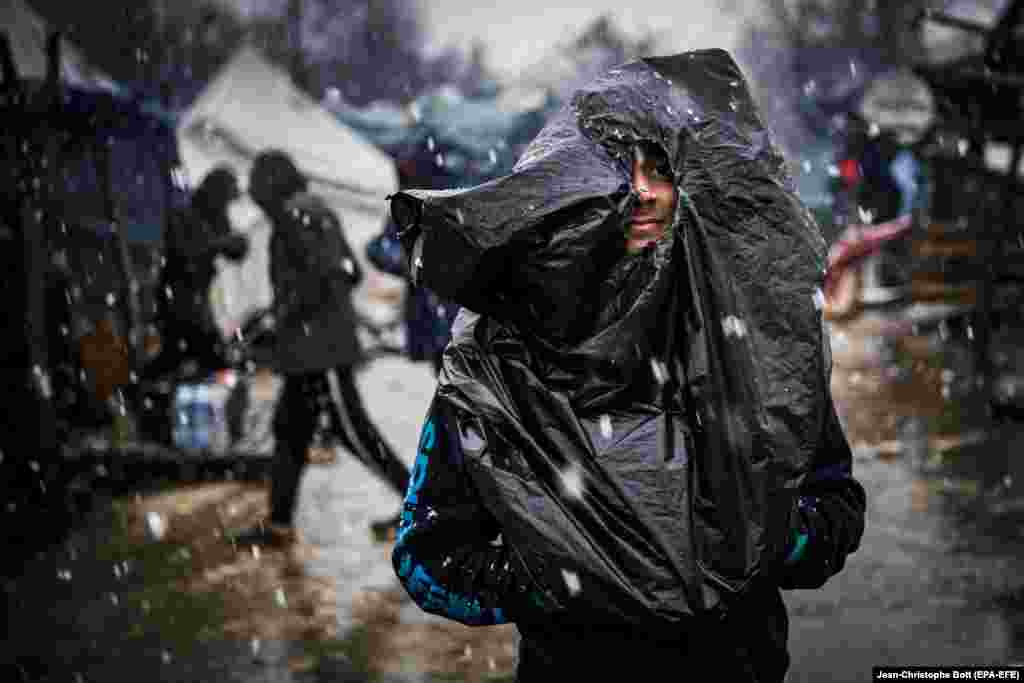 A migrant covers himself with a plastic bag during a rainstorm at the Vucjak refugee camp outside Bihac, Bosnia-Herzegovina. According to local media, hundreds of people remain at the camp even after international officials called for it to be shut down. (epa-EFE/Jean-Christophe Bott)